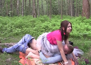 A hot woman is rendition a one night observe with a horny dude in the forest
